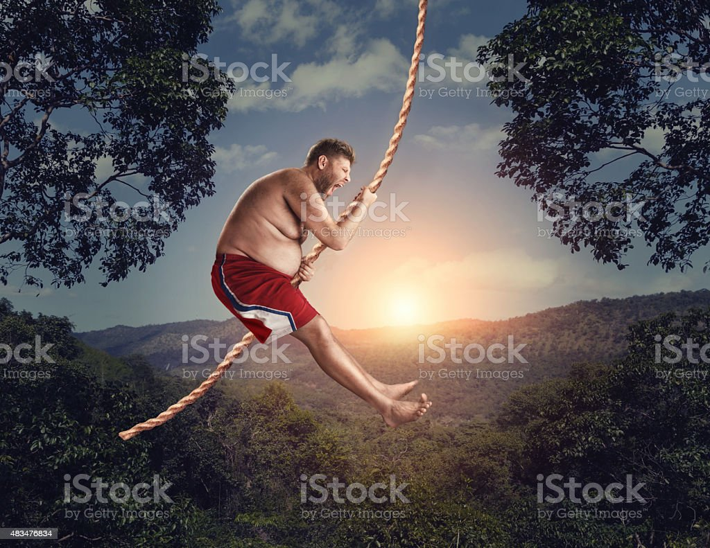Man flying in the air by rope stock photo