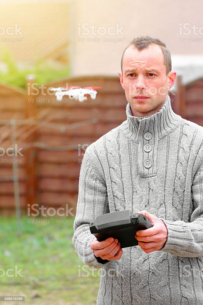 Man flying small drone using remote stock photo