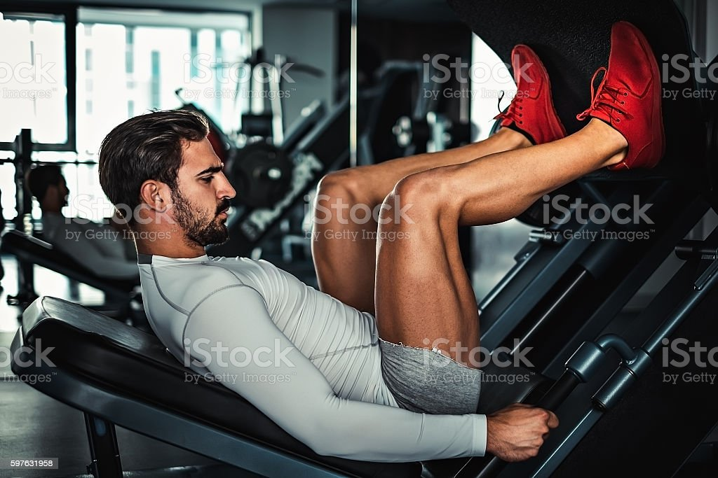 Man focused on training legs on the machine stock photo