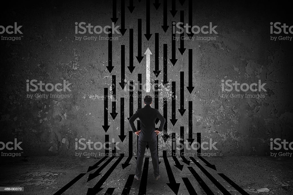 Man focusing on a white arrow going in different direction stock photo