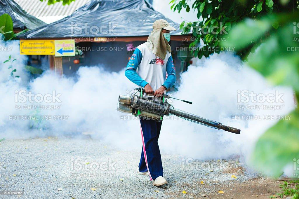 Man fogging mosquito spray in a public park stock photo