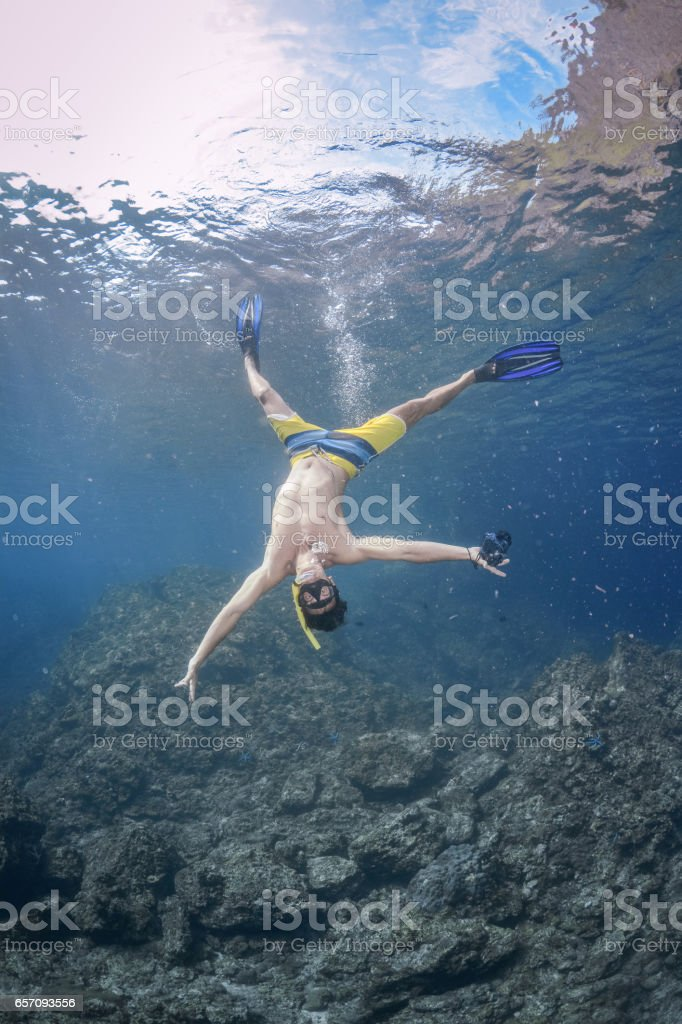 Man free diving head over in the Ocean stock photo