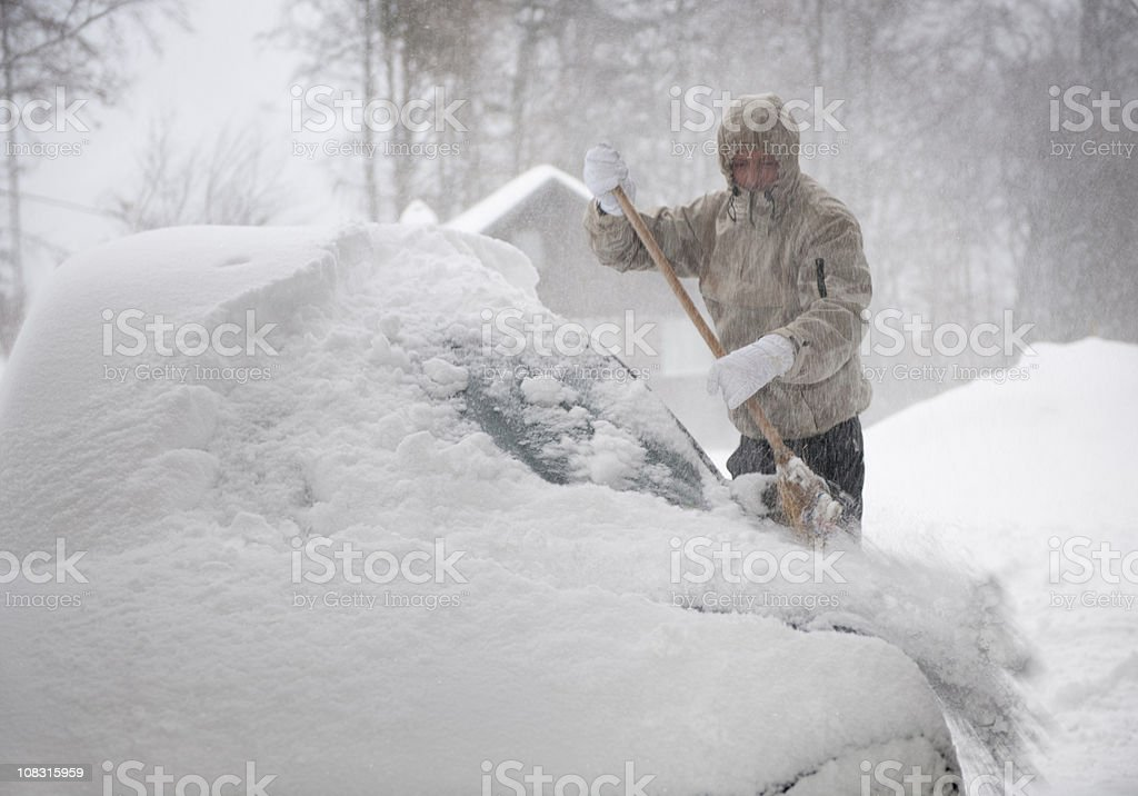 Man freeing car from snow in the a blizzard (XXXL) stock photo