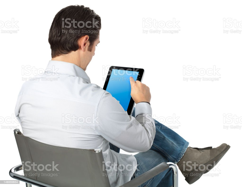 Man From Behind Sitting in Chair Casually Browsing Smart Tablet royalty-free stock photo