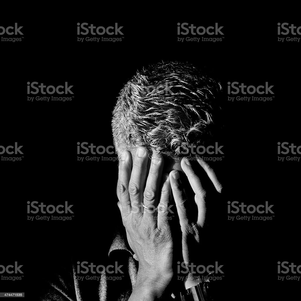 Man Frustrated and ashamed with hands on face stock photo