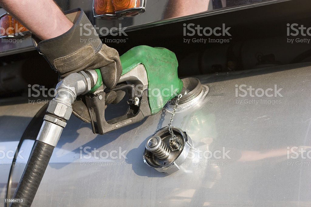 A man fuelling up a freight transport truck stock photo