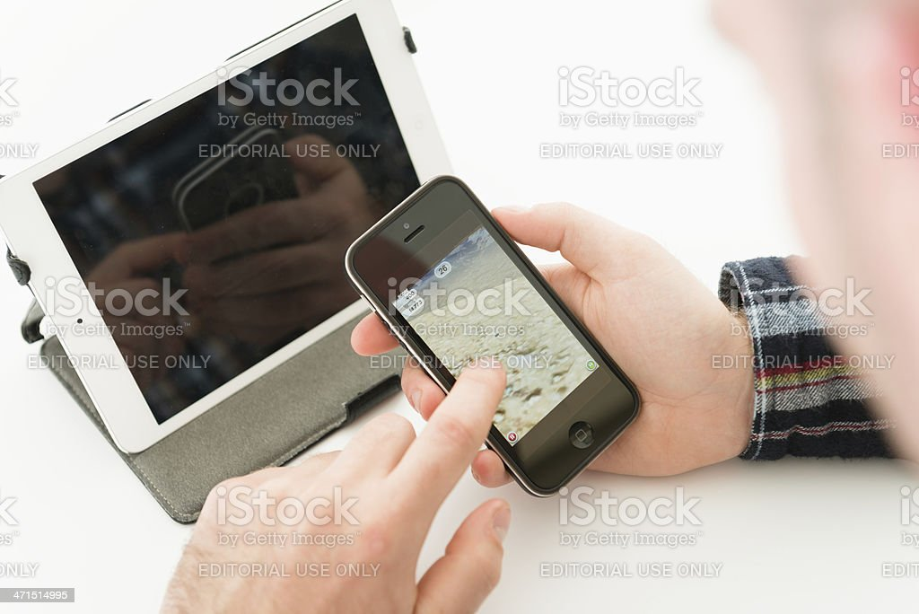 Man gaming with golf app and new Apple Iphone 5 royalty-free stock photo