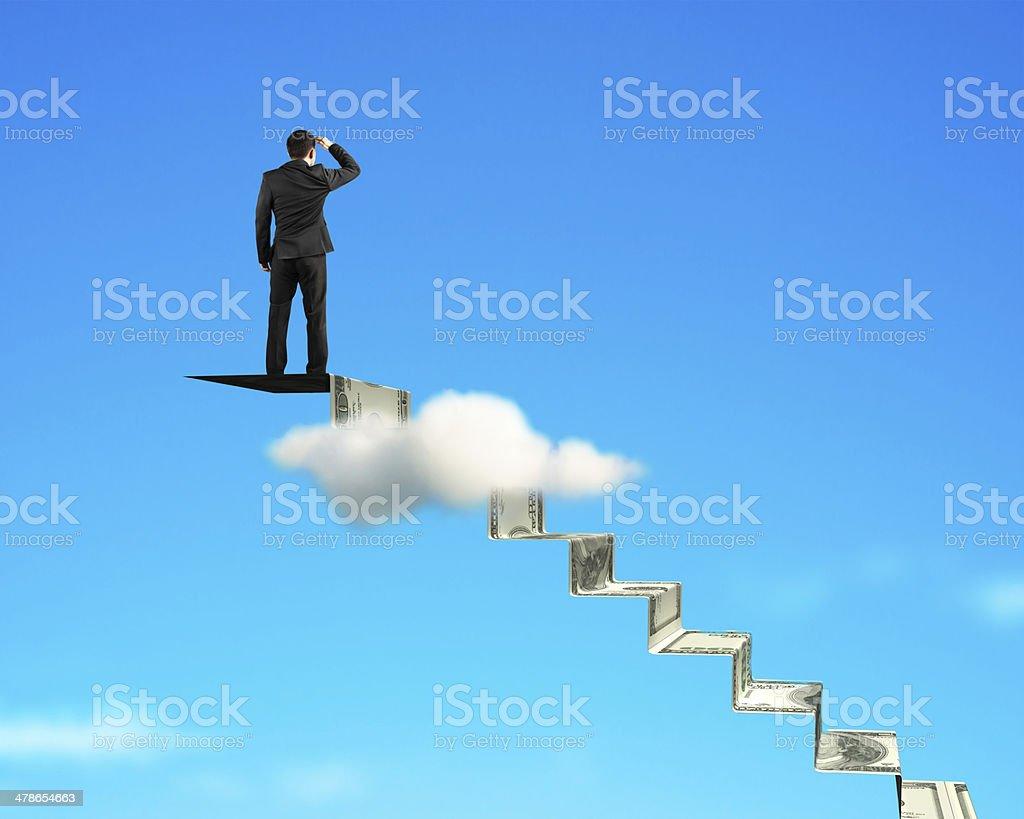 Man gazing on top of money stairs stock photo