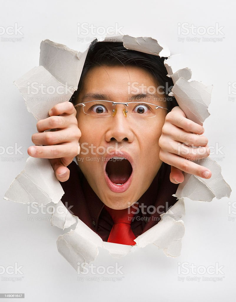 Man gazing surprisingly from hole in wall royalty-free stock photo