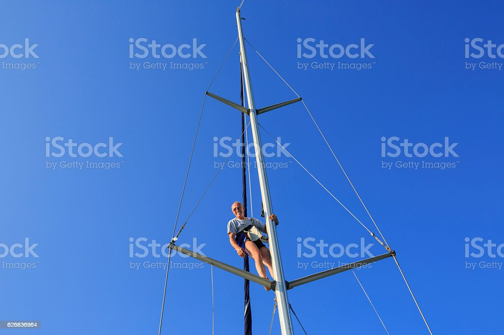 Man get up on the mast and do repairations stock photo