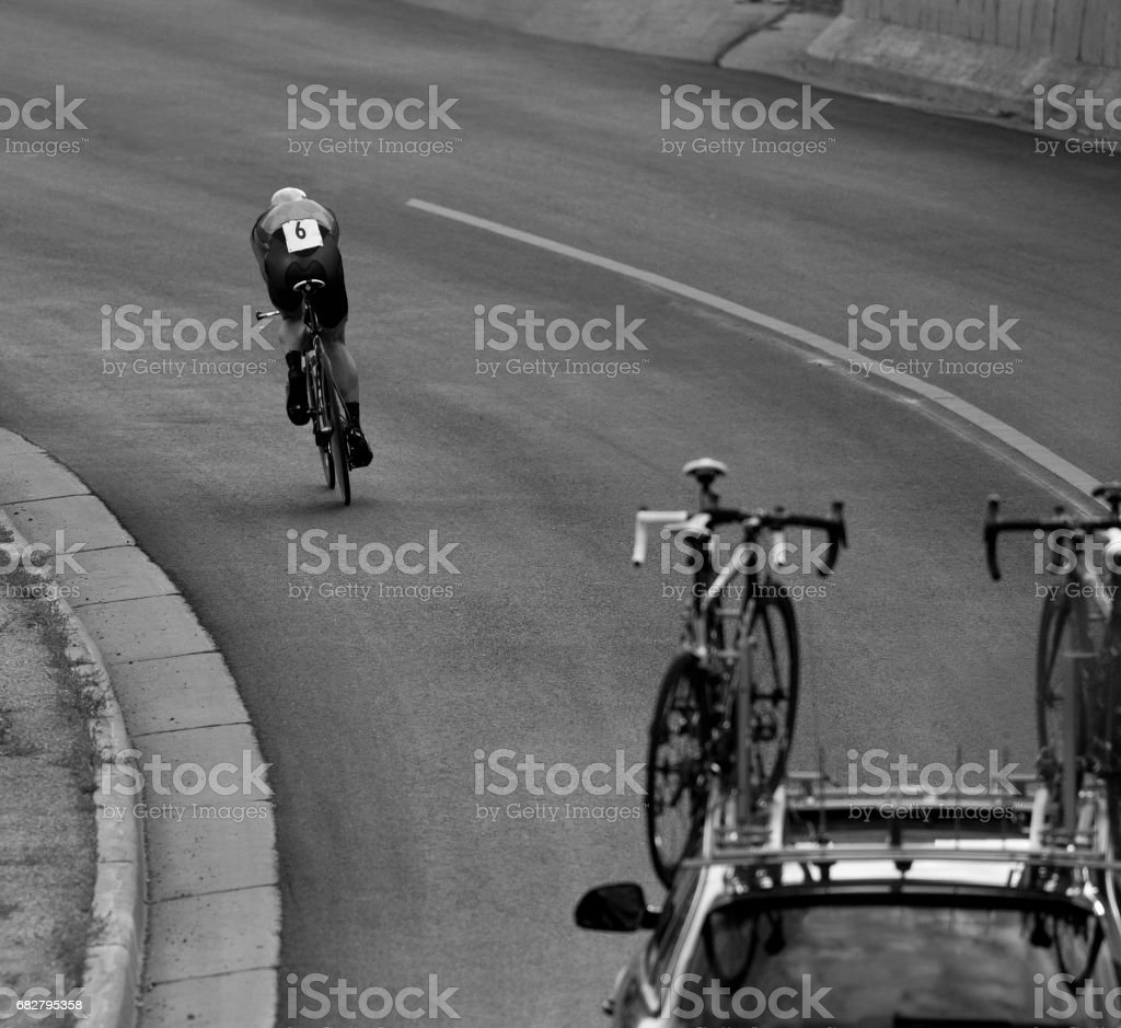 A man gets into an aerodynamic position while riding a downhill in a time trial during a profession road bike race. stock photo
