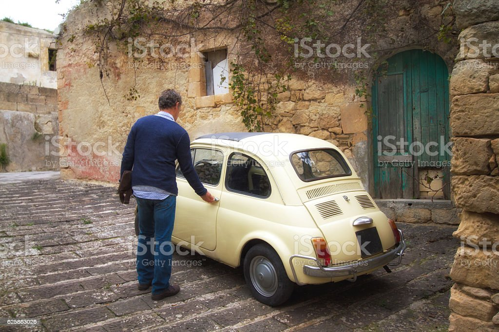 Man Gets Into Cute Little Yellow Vintage Car, Italy stock photo