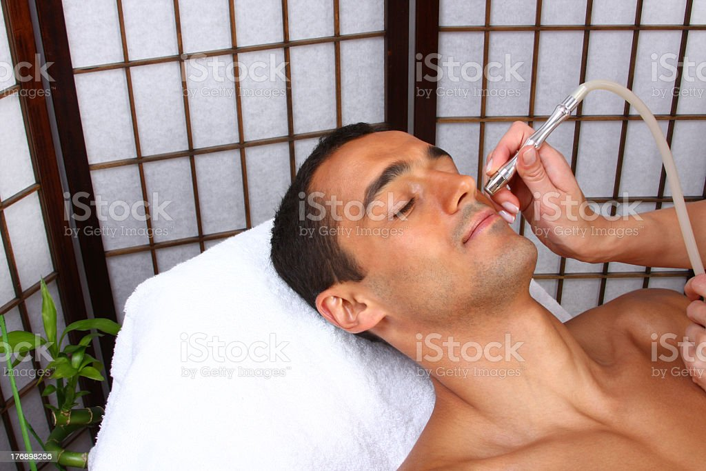 Man getting a facial massage and enjoying it royalty-free stock photo