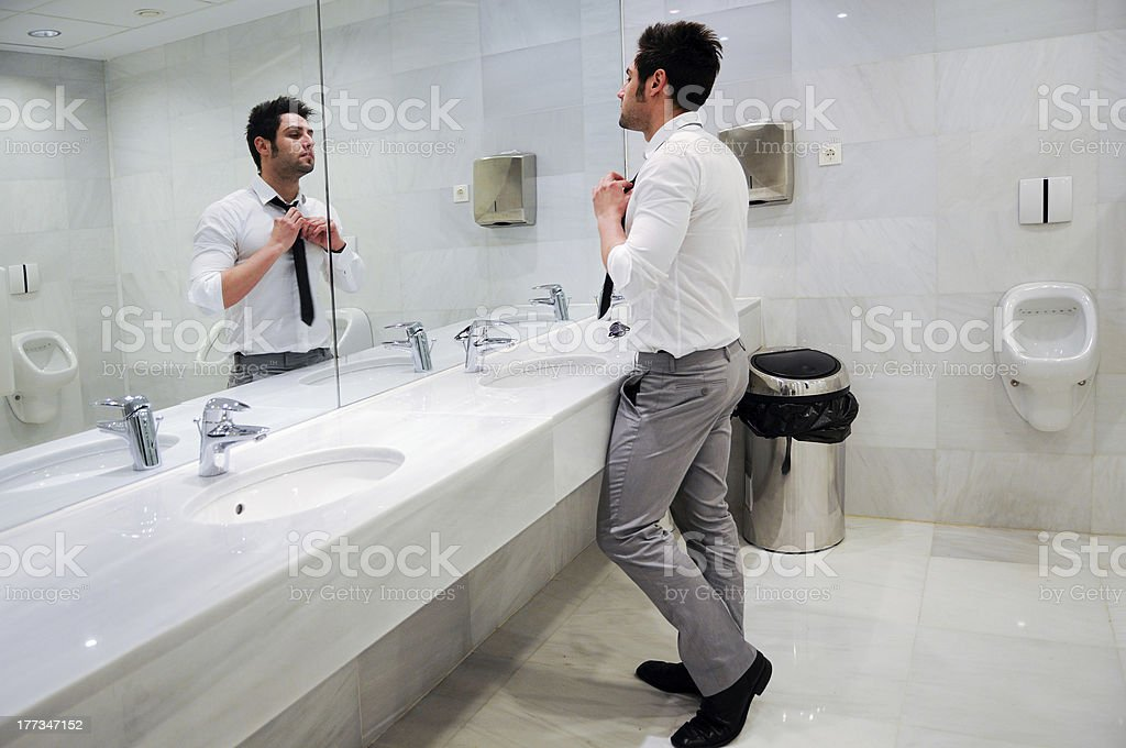 Man getting dressed in a public restroom with mirror stock photo