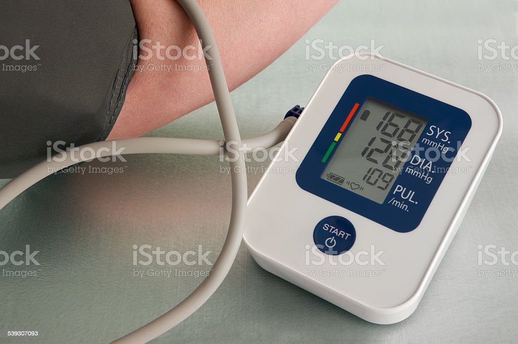 Man getting high blood pressure reading from digital monitor stock photo
