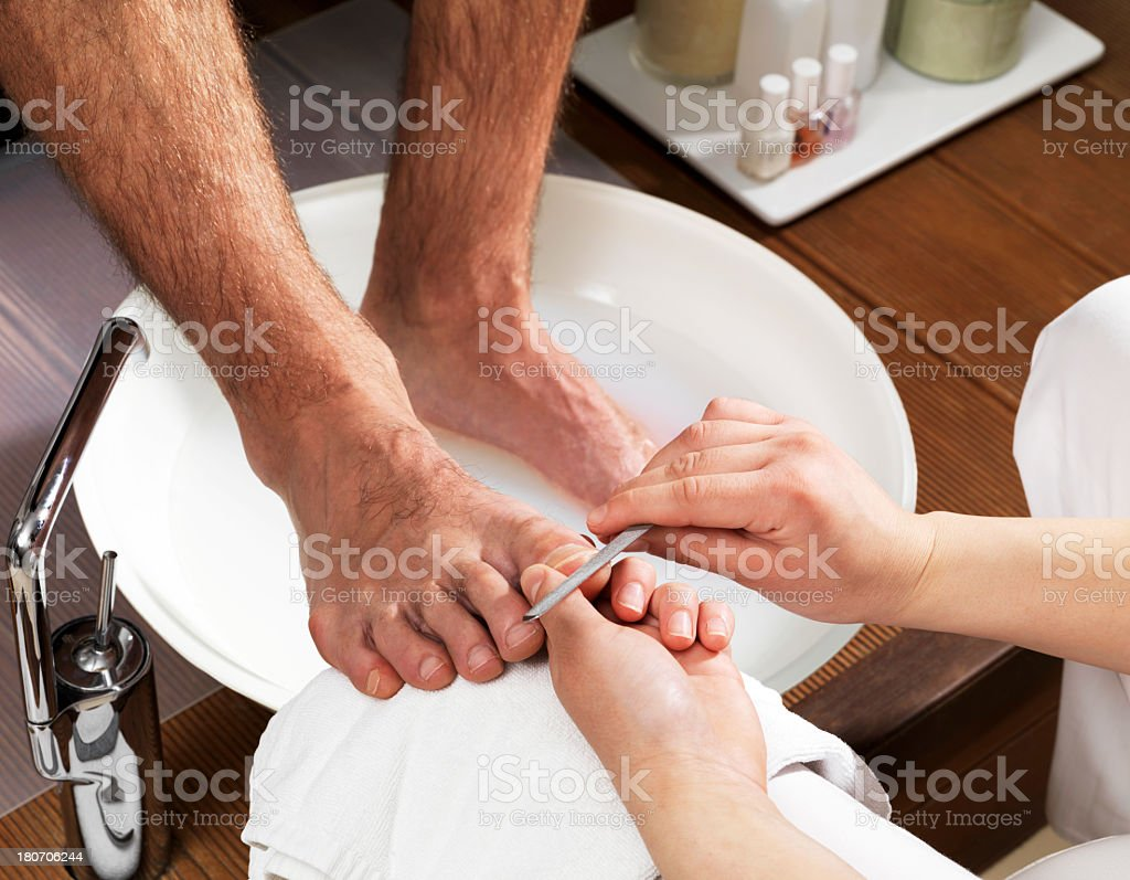A man getting his feet touched up stock photo