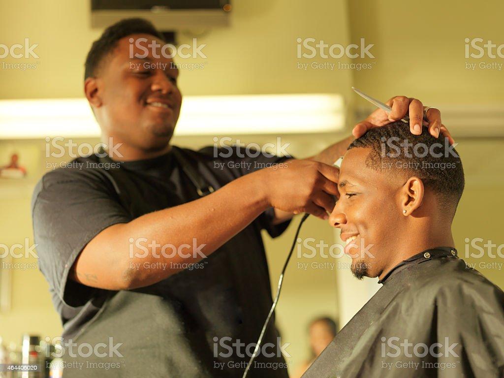 man getting his hair cut at barber shop stock photo