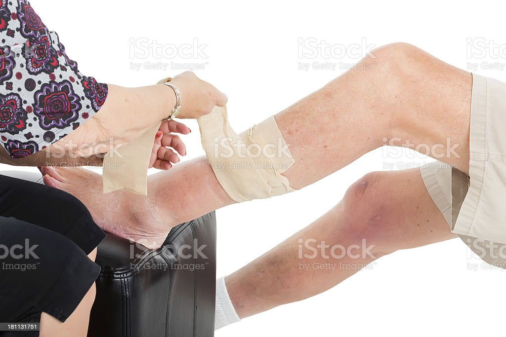 Man Getting his leg wrapped in a bandage royalty-free stock photo