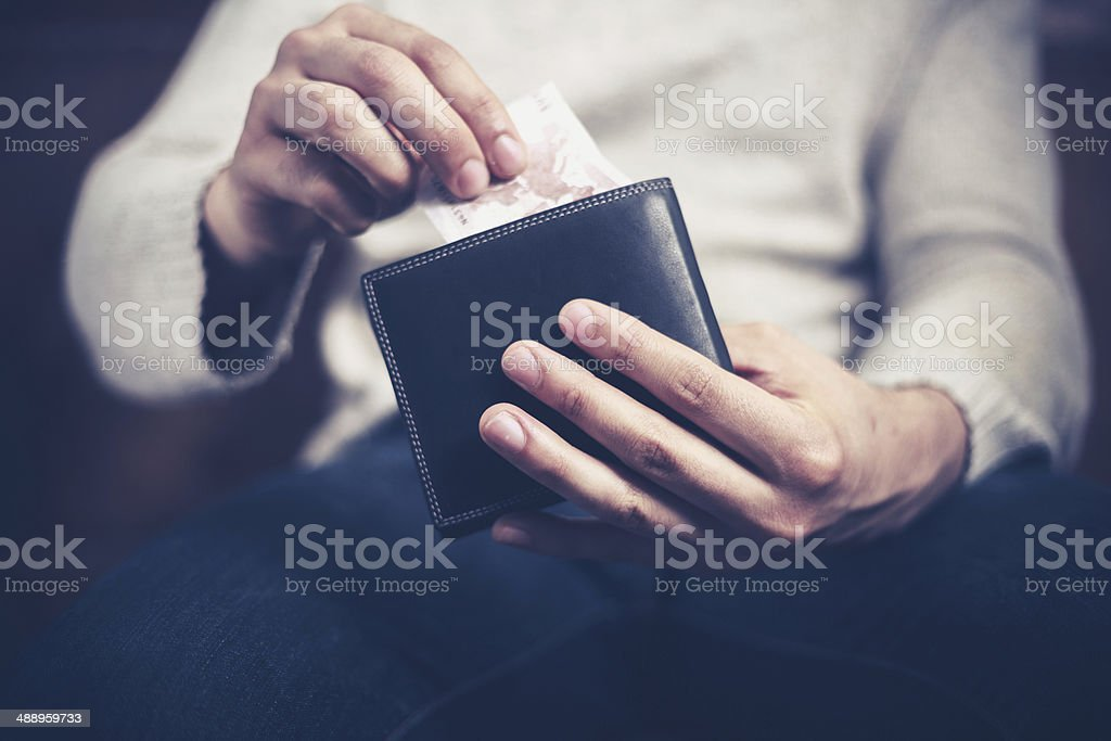 Man getting money out of his wallet stock photo
