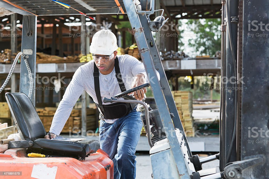Man getting on forklift stock photo