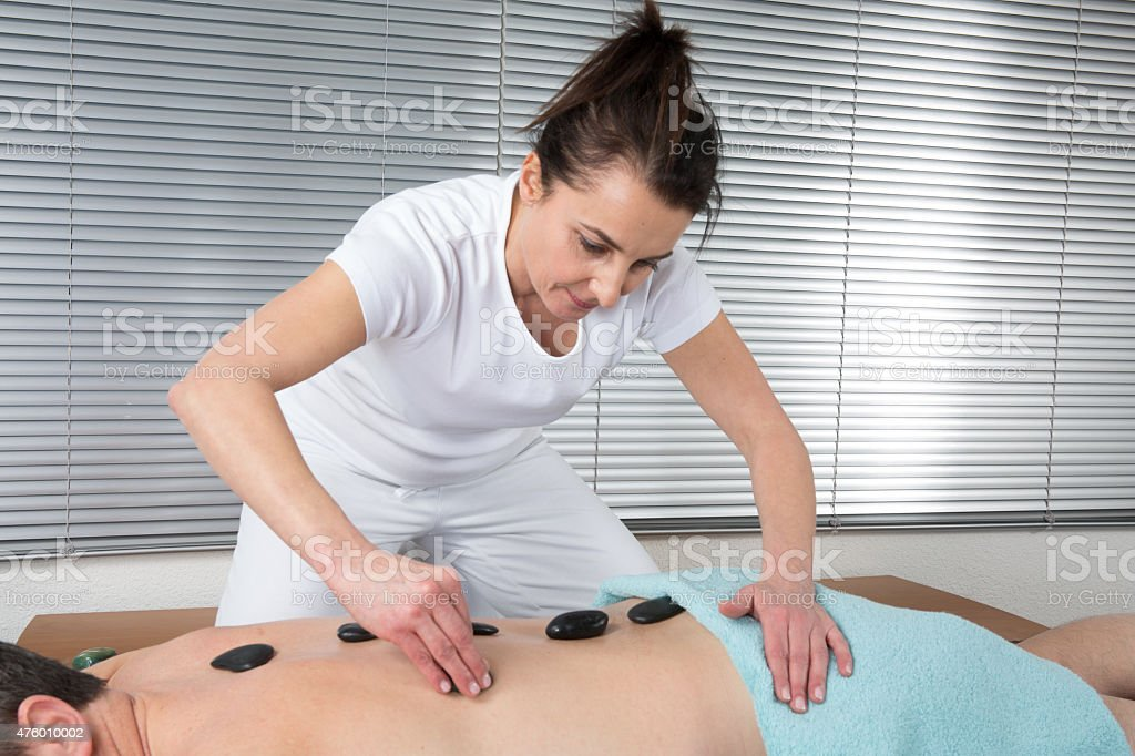 Man getting stone therapy massage in spa center stock photo