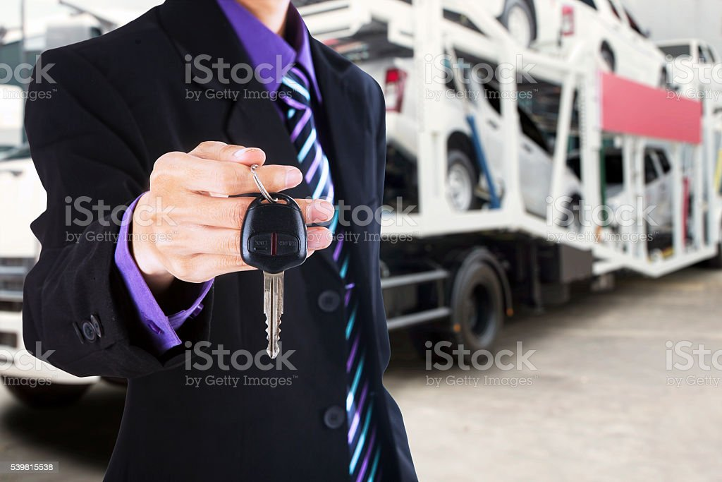 Man gives a car key with trailer truck background stock photo
