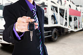 Man gives a car key with trailer truck background