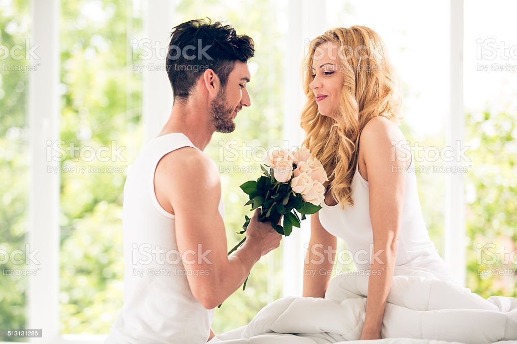 Man gives bouquet of roses to woman stock photo