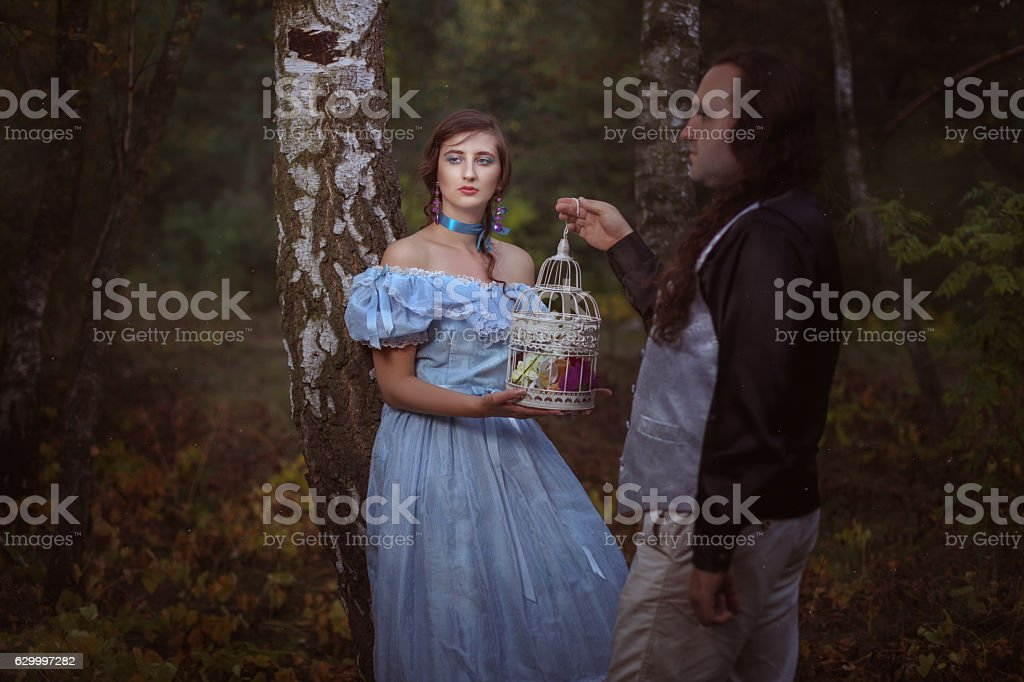 Man gives the woman a cage. stock photo