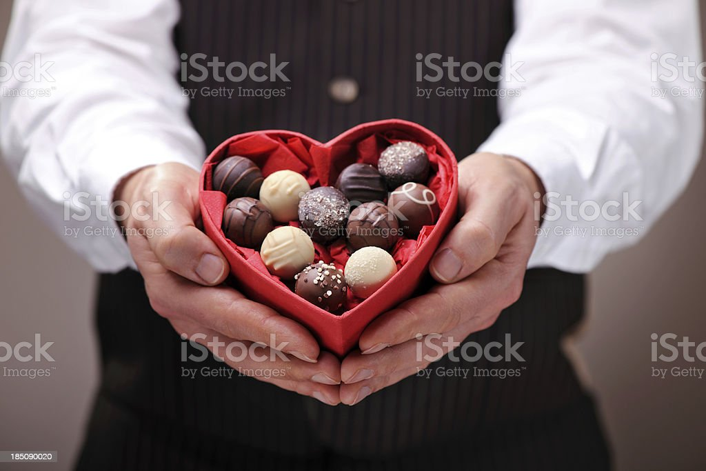 Man giving a heart shaped chocolate praline box stock photo