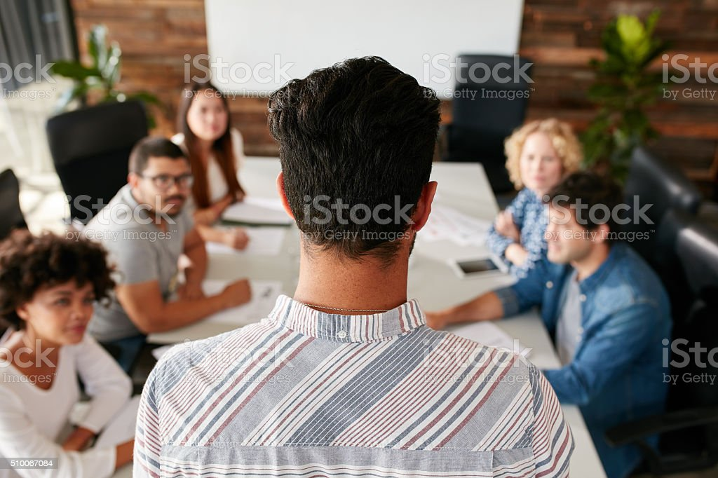 Man giving business presentation to colleagues in conference room stock photo