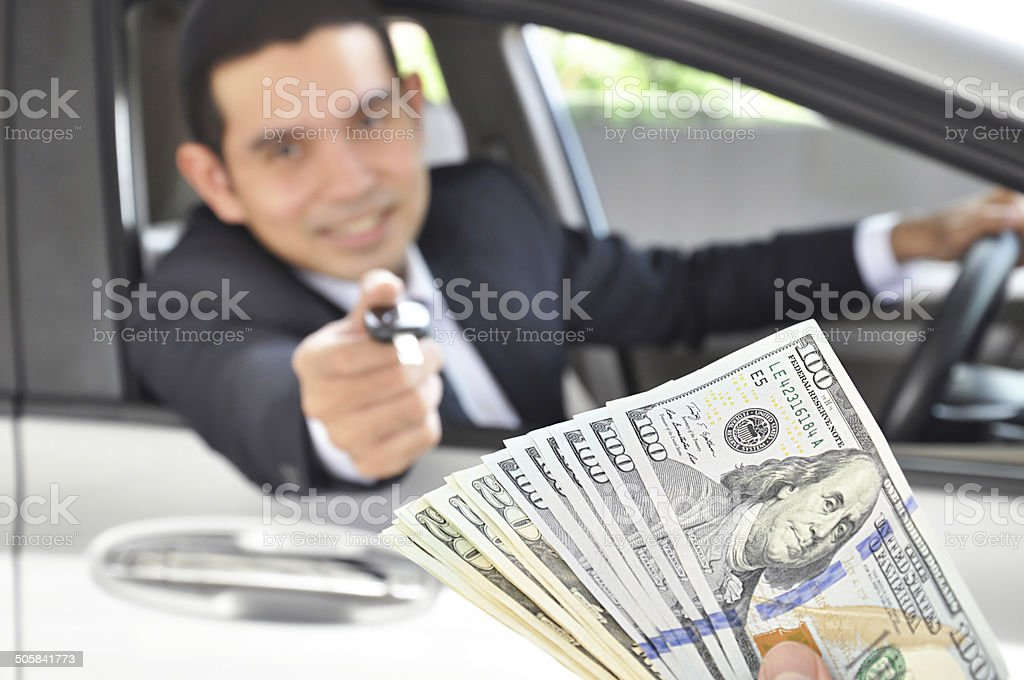 Man giving car key exchanging with money  - car pawn stock photo