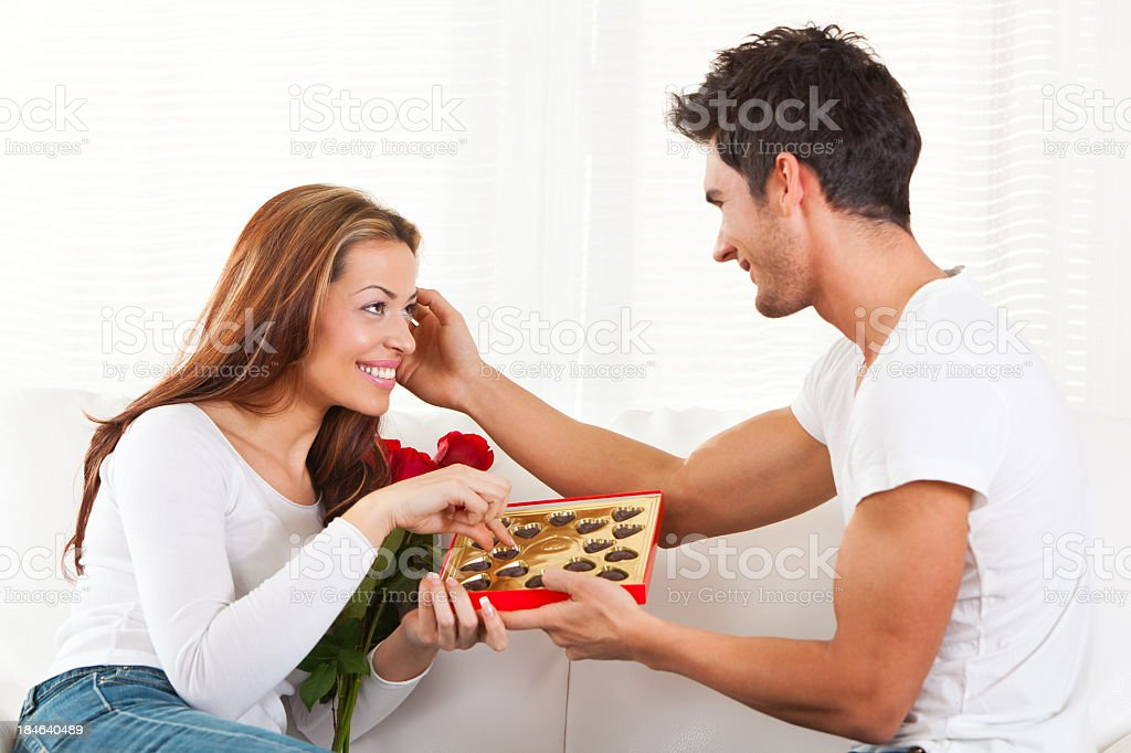 Man giving chocolate candies and red roses to girl royalty-free stock photo