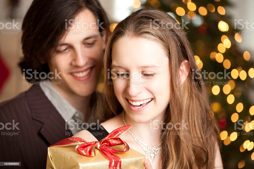Man Giving Christmas Present to His Wife at Home royalty-free stock photo