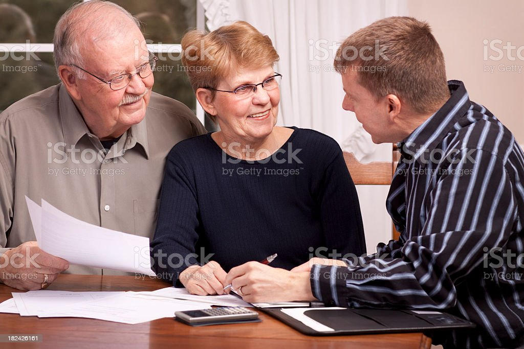Man giving financial advisor to senior couple smiling stock photo