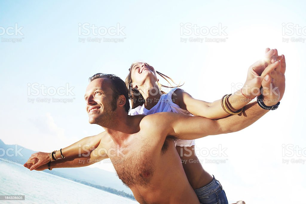 Man giving his girlfriend a piggyback ride on the beach. royalty-free stock photo