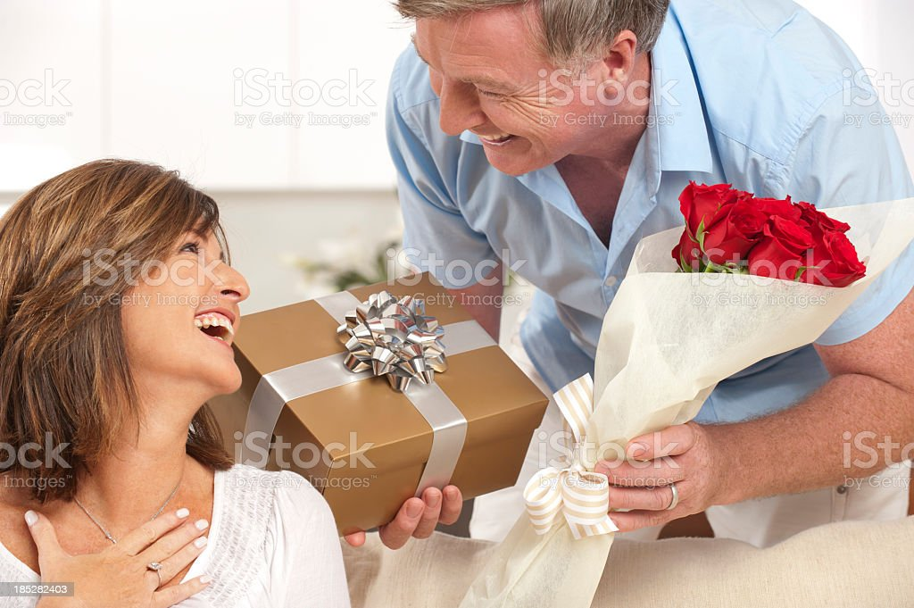 Man giving his happy wife a gift and red roses
