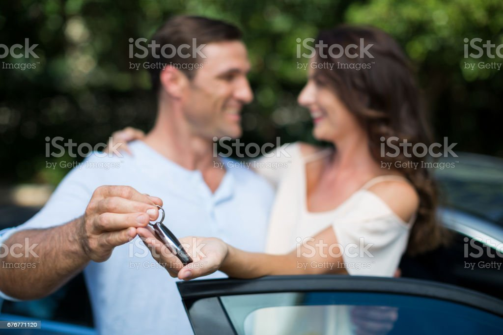 Man giving key to woman by car stock photo