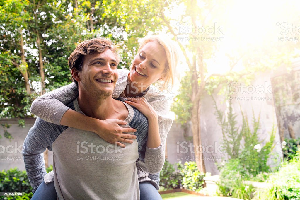 Man giving piggyback ride to woman in backyard stock photo
