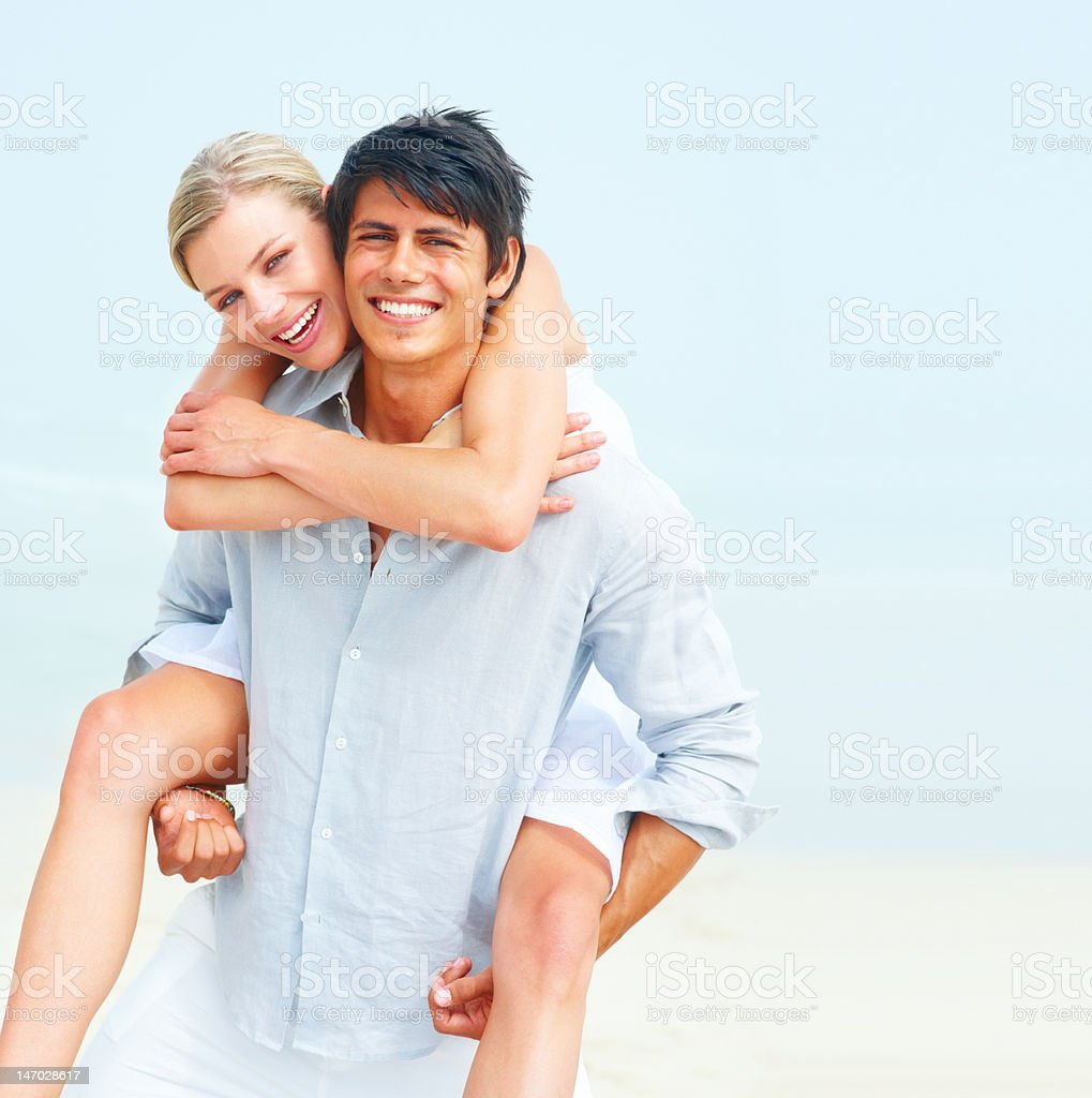 Man giving piggyback to his girlfriend on the beach royalty-free stock photo