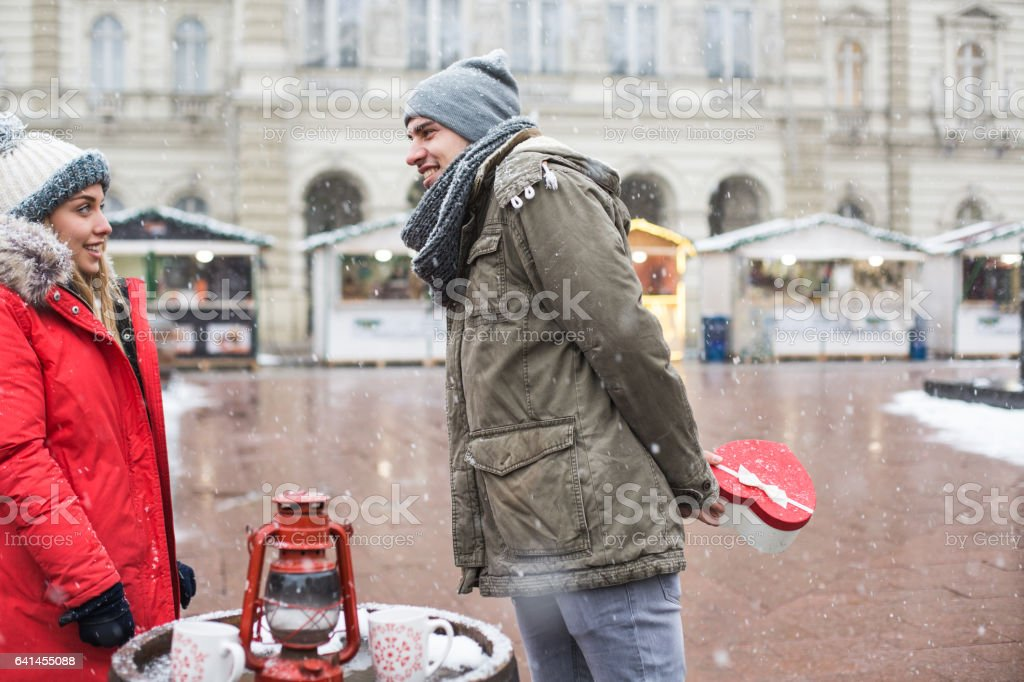 Man giving present to his girlfriend on Christmas market stock photo