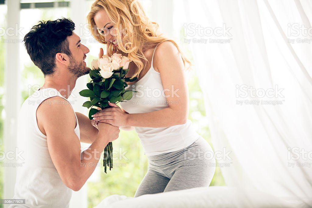 Man giving roses to his wife stock photo