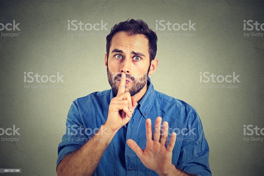 man giving Shhhh quiet, silence, secret gesture stock photo