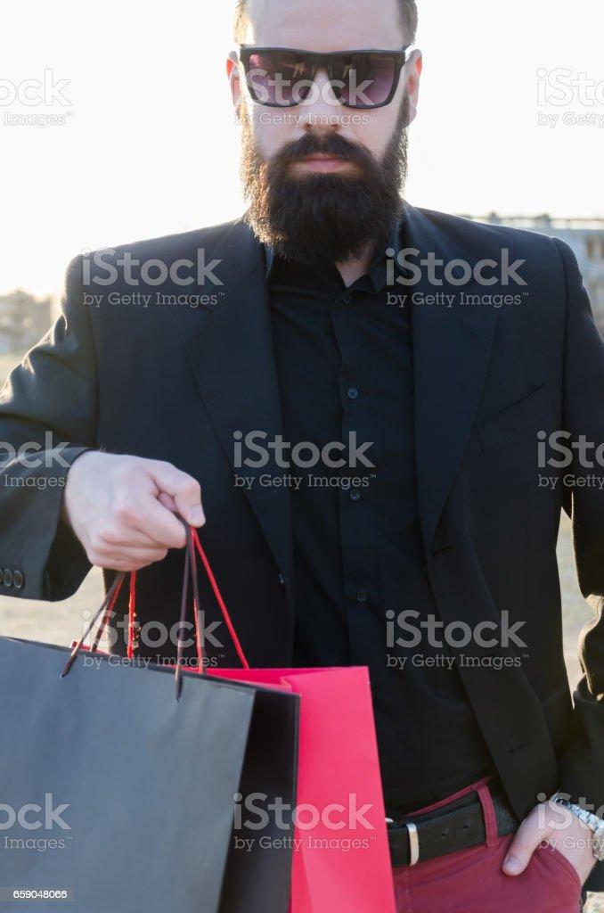 man giving shopping bags at the camera stock photo