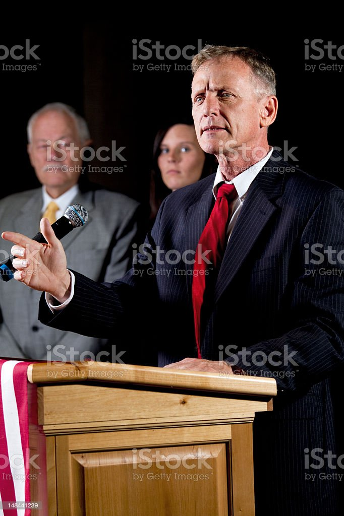 Man giving speech at podium with American flag royalty-free stock photo