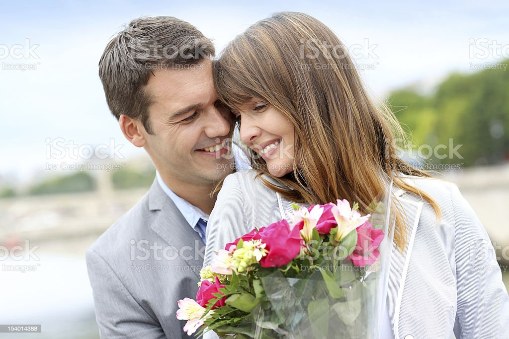 Man giving woman a bunch of flowers stock photo