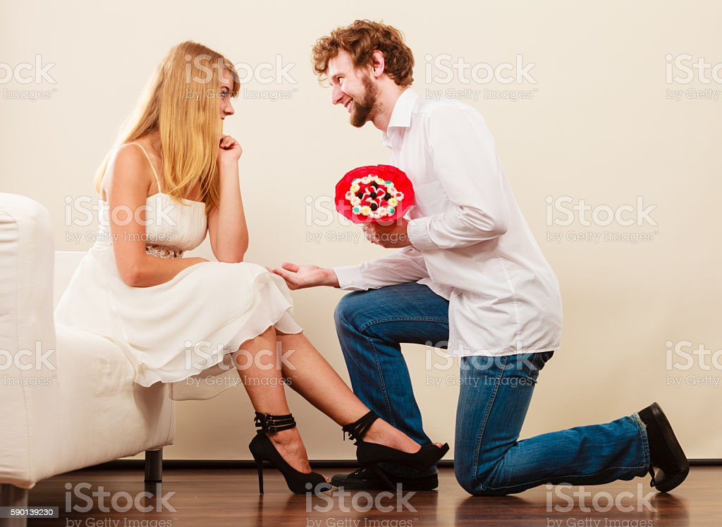 Man giving woman candy bunch flowers. Happy couple stock photo