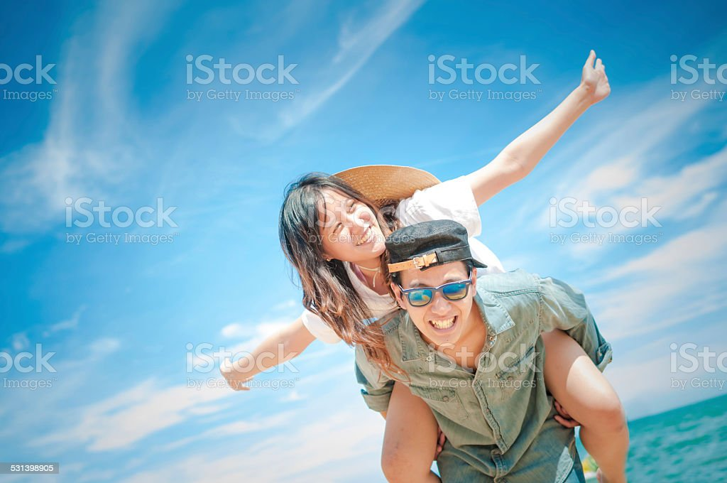 Man giving woman piggyback ride at the beach. stock photo