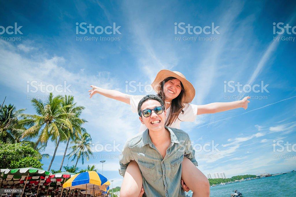 Man giving woman piggyback ride at the beach. stock photo