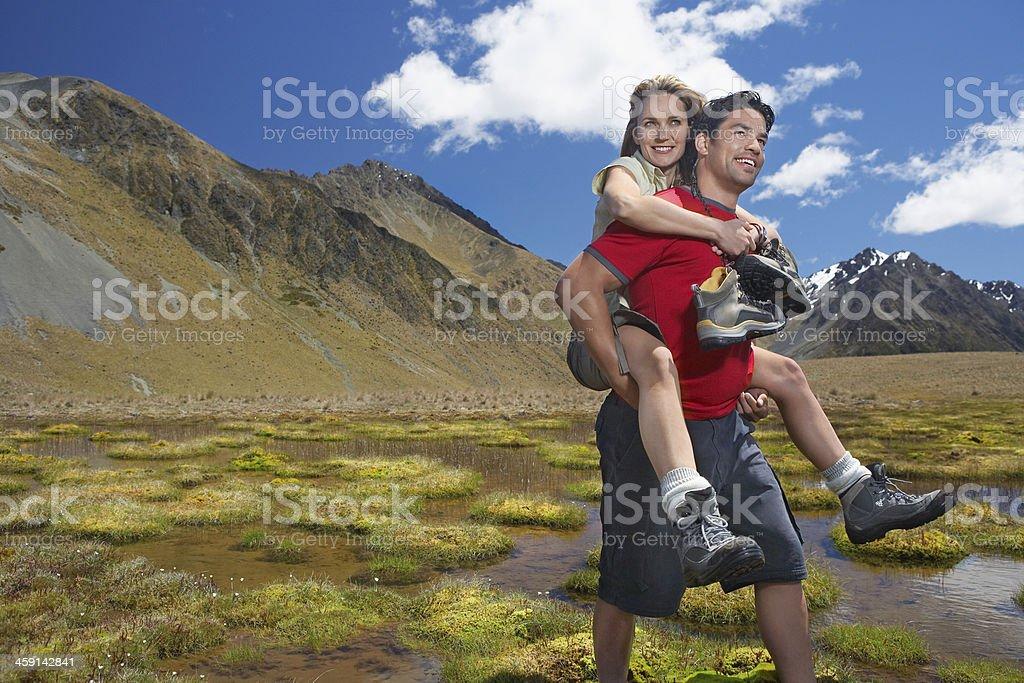 Man Giving Woman Piggyback Ride through Mountain Pond royalty-free stock photo
